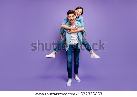 Full length photo of romantic funny funky married people have fun date hug piggyback  enjoy date wear stylish trendy clothes isolated over purple color background