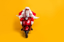 Full length photo of serious santa claus in red hat drive his modern motorbike ride north-pole for christmas x-mas celebration wear shirt suspenders isolated yellow color background
