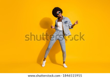 Full length photo of shiny lovely young lady wear casual denim outfit smiling dancing isolated yellow color background