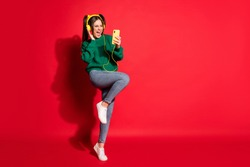 Full length photo of shiny young woman dressed green knitted sweater headset dancing singing isolated red color background