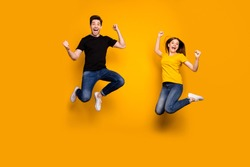 Full length photo of sporty guy and lady couple jumping high active way of life celebrating first win place competition wear casual jeans t-shirts isolated yellow color background