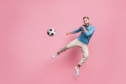 Full length photo of sweet strong young man dressed blue sweater jumping high kick foot ball isolated pink color background