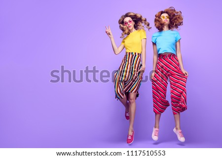 Full-length photo of Two Cheerful fashionable Girl dance Jumping in Studio on Purple. Young happy Beautiful Woman in Trendy summer fashion Outfit. Carefree shapely Sisters Friends Having Fun