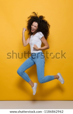 Full length photo of young woman 20s with curly hair having fun and jumping isolated over yellow background