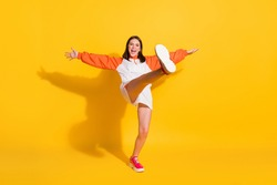 Full length photo portrait of girl standing on one leg kicking isolated on vivid yellow colored background