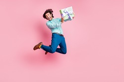 Full length photo portrait of happy man holding wrapped present box jumping up isolated on pastel pink colored background