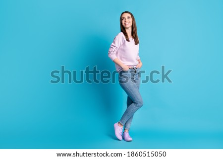 Full length photo pretty charming cute lady good mood look side empty space interested hold hands jeans pockets dreamer wear casual sweatshirt pullover isolated blue color background Stock photo ©