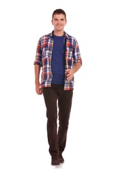 full length picture of a casual friendly young man walking towards the camera �¢?? isolated over a white background