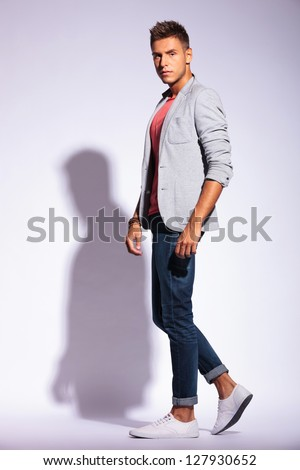 full length picture of a casual young man posing sideways and looking at the camera, over a light background with hard shadow