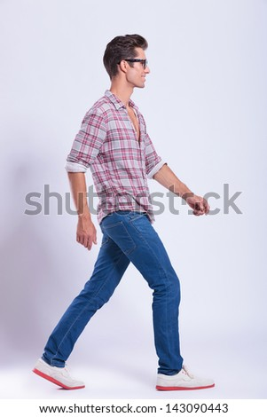 full length picture of a casual young man walking to the side of the camera and looking forward. on gray background