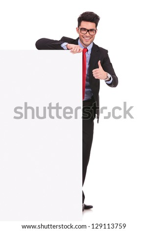 full length picture of a young business man holding a blank board and showing thumbs up sign while smiling to the camera on white background