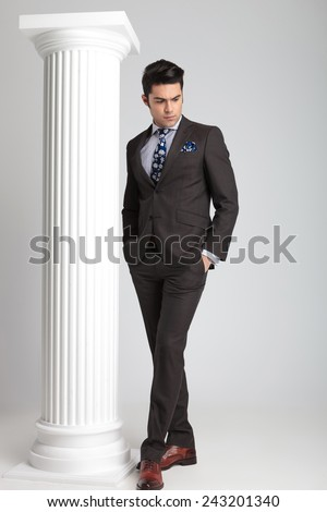 Full length picture of a young business man looking down while holding both hands in his pockets.