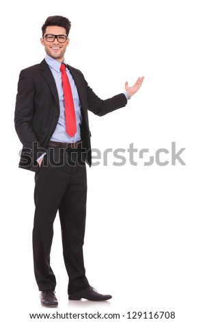 full length picture of a young business man presenting something in the back with one hand in his pocket while looking at the camera with a smile on his face, on white background