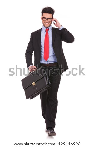 full length picture of a young business man walking forward with a briefcase in one of his hands and talking at the phone while smiling to the camera on white background