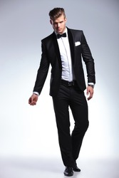 full length picture of an elegant young fashion man in tuxedo posing, while looking at the camera. on gray background