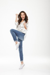 Full-length picture of brunette woman in casual with brown hair clenching fists like winner rejoicing with happy emotions isolated over white wall