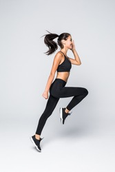 Full length picture of jumping fitness woman over gray background