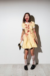 Full length picture of mad happy zombie woman in dress holding an axe and looking at the camera over white background