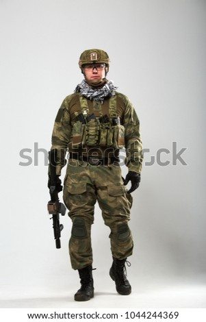 Full-length picture of soldier with gun in his hand