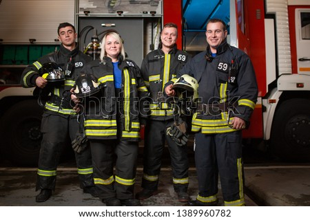 Full-length picture of three young fire men and woman on background of fire truck