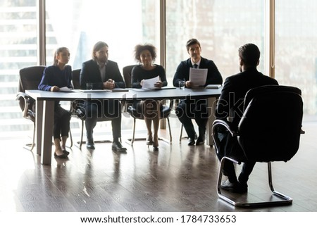 Full length pleasant smiling multiracial diverse human resources managers sitting at table at distance from male candidate, asking questions about working experience, first impression hiring concept.