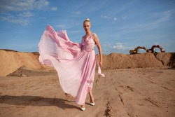 Full length portait of a girl with hairstyle dressed in flying pink dress, posing in a desert, at sunset background.