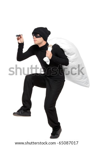 Full length portait of a robber with a bag and flashlight in hands isolated against white background