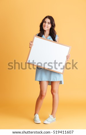 Full length portrait a smiling brunette woman in blue dress holding white blank board isolated on the orange background