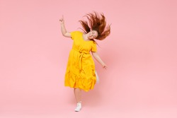 Full length portrait cheerful young redhead plus size body positive chubby overweight woman in yellow dress posing jumping dancing with fluttering hair isolated on pastel pink color background studio