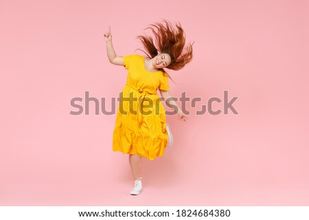 Full length portrait cheerful young redhead plus size body positive chubby overweight woman in yellow dress posing jumping dancing with fluttering hair isolated on pastel pink color background studio ストックフォト ©
