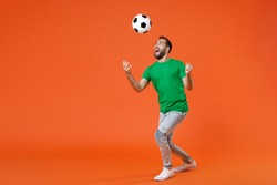 Full length portrait excited young man football fan in green t-shirt cheer up support favorite team throwing soccer ball isolated on orange background studio. People sport leisure lifestyle concept