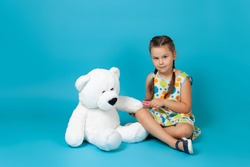full-length portrait of a beautiful girl sitting cross-legged on the floor and pulling a splinter out of the paw of a white teddy bear with tweezers isolated on a blue background.
