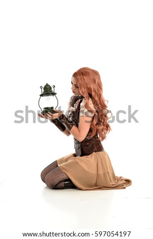 Stock Photo full length portrait of a beautiful girl wearing steampunk outfit, kneeling pose isolated on white background.