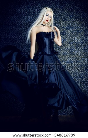 Full length portrait of a beautiful gothic woman in long black dress. Antique castle style. Halloween.