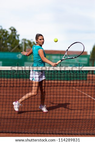 Full length portrait of a beautiful woman tennis player prepared for a backhand stroke