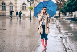 Full length portrait of a beautiful young woman talking on the mobile phone and holding an umbrella in the city.