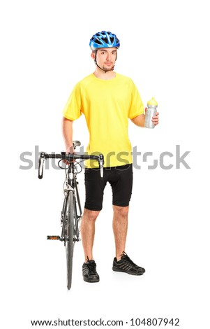 Full length portrait of a bicyclist posing next to a bicycle and holding a bottle isolated on white background