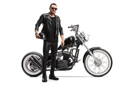 Full length portrait of a biker in leather jacket and pants with a chopper motorbike isolated on white background