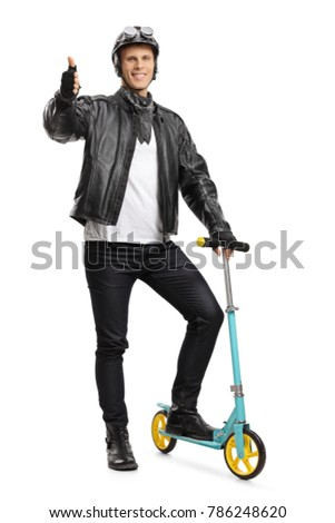 Full length portrait of a biker with a scooter making a thumb up sign isolated on white background