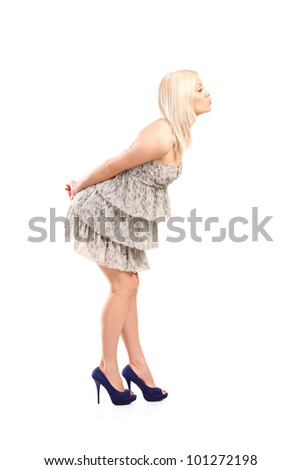Full length portrait of a blond woman wearing dress giving kisses isolated against white background