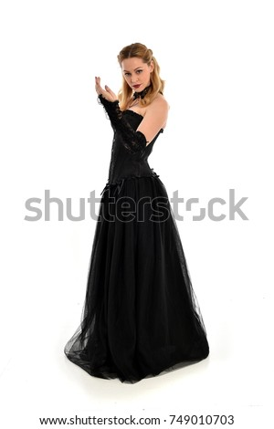Stock Photo full length portrait of a blonde girl wearing black gothic gown. standing pose, isolated on white background.
