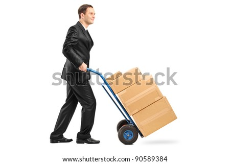 Full length portrait of a businessman pushing a hand truck full with cardboard boxes isolated on white background
