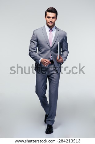 Full length portrait of a businessman walking with latpop over gray background