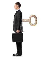 Full length portrait of a businessman with wind-up key in his back isolated against white background