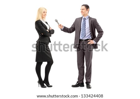 Full length portrait of a businesswoman and male reporter having an interview, isolated on white background