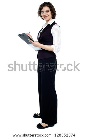 Full length portrait of a businesswoman taking down notes.