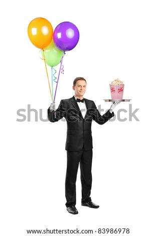 Full length portrait of a butler carrying a tray with a popcorn box on it and balloons isolated on white background