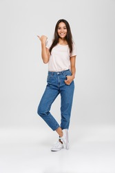 Full length portrait of a casual pretty asian woman standing and pointing finger away at copy space isolated over white background