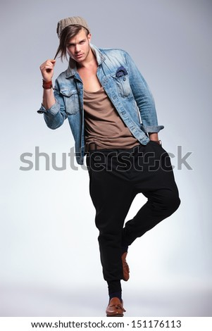 full length portrait of a casual young man balancing on one leg while holding a hand in his pocket and pulling his hair with the other. on gray studio background