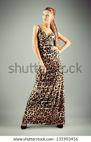 Full length portrait of a charming fashionable woman posing over gray background.